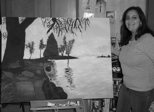 A picture of Phase II Scholar Amanda  with one of her recent paintings.