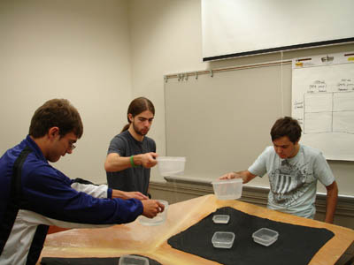 Picture of. Scott, Cory, and Peter using plastic containers of water to demonstrate climate change.