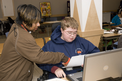 Picture of Erik working on his laptop with Oscar pointing to a handout.
