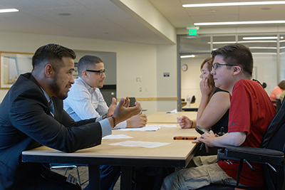 An instructor discusses across a table with a high school student.
