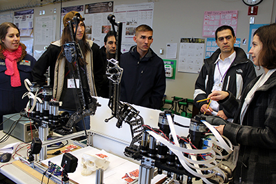 A member of the robotics lab explains the workings of a robot to participants.