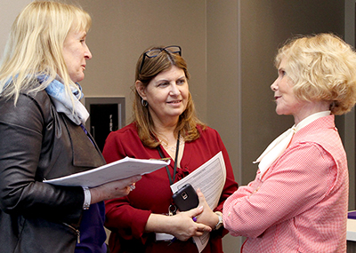 Sheryl Burgstahler talks to two participants.