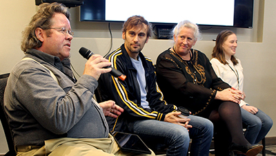 A panel member speaks into a microphone while other panelists look towards him.