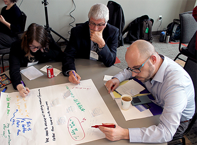 Participants write their input to a statement on a large post-it note.