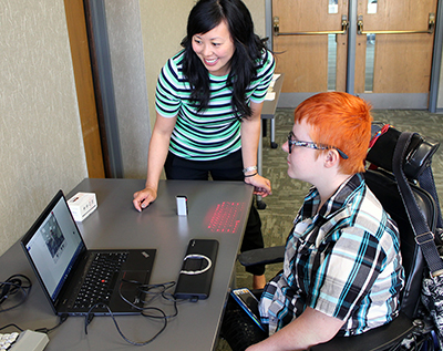 An Assistive Technology Specialist shows off facial tracking software to a University of Washington student.