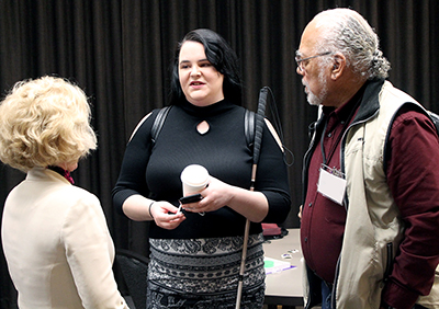 PI Sheryl Burgstahler talks to two individuals at an event.