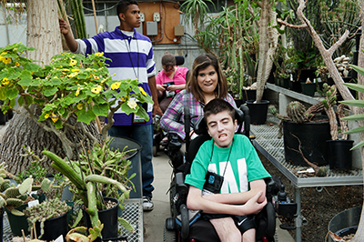 Students with disabilities look at plants in a greenhouse.