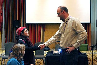 A panelist shakes hands with AccessComputing Co-PI Jacob Wobbrock.