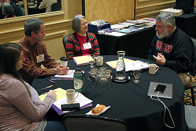 A group of participants discuss issues around the table.