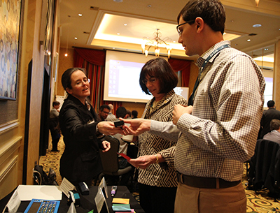 A participant sharing interest in the accessible science equipment with another participant.