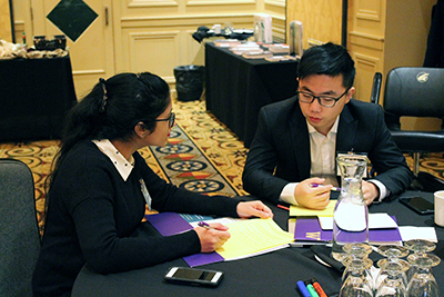 Two participants write down ideas to a discussion question.