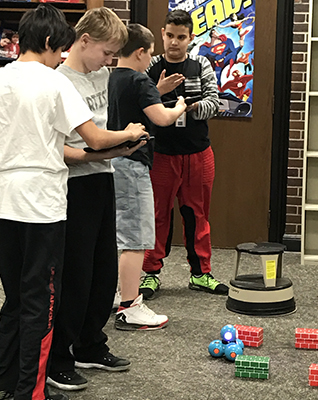 Deaf Kids Code participants test their code as they make a robotic car navigate an obstacle course.