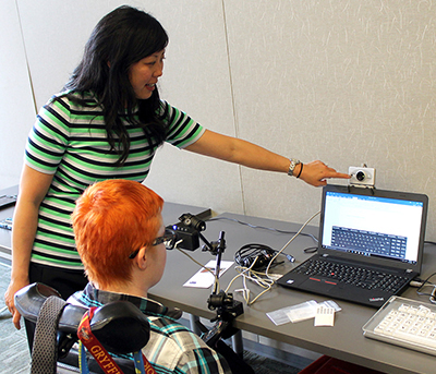 A mentor shows a student how to use an eye tracking camera.