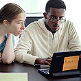 Image of a mentor helping a student on a laptop