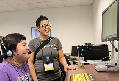 A staff members teaches a students how to use a voice to text program.