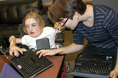 An instructor works with a student in a wheelchair with a laptop.
