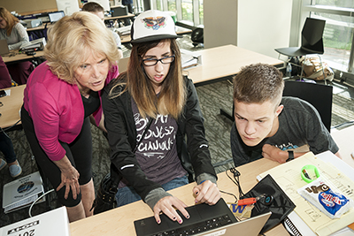 An instructor helps students with online research.