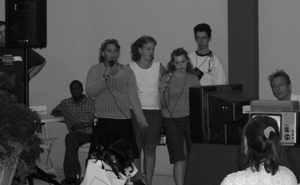 Image of students with disabilities at a podium speaking to an audience.
