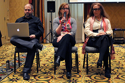 Three panelists sit at the front of the room. One speaks into the microphone.