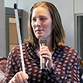 Postdoctoral researcher Cynthia Bennett holds her cane and a microphone while presenting.