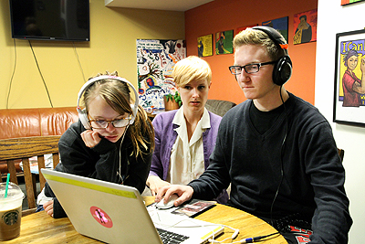 Two students work together on a computer with the help of a mentor.