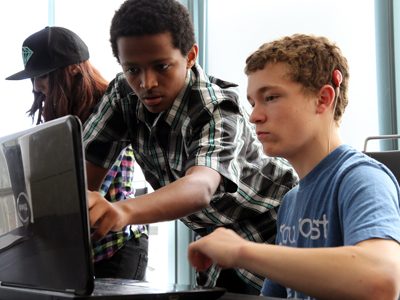 Two students view a computer screen.