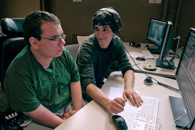 A student in a wheelchair looks at a computer while another student explains something.