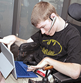 A student uses a headset and a tablet with an attachable keyboard.