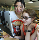 Two students collaborate on a computer project