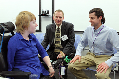 A student in a wheelchair chats with two ERC instructors.