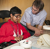 An educator shows a student some neurobiology materials.