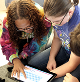 Two deaf students use a tablet.