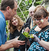 A blind student feels a venus fly trap that an instructor is handing her.
