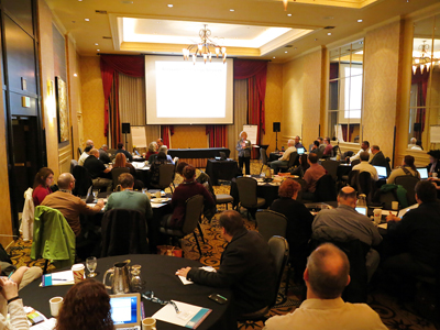 An overview of the event room, showing all of the participants watching a presentation.