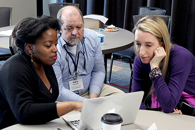 Three participants view resources on a laptop during the AccessEngineering capacity building institute.