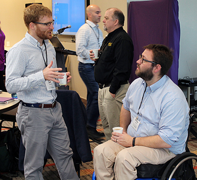 Two participants discuss ideas over coffee at the AccessEngineering capacity building institute.