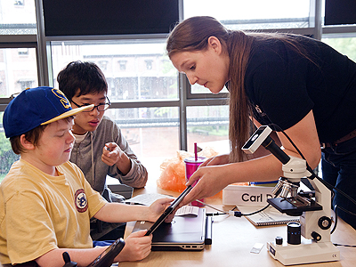 A teacher from Exo Labs working with two students at Summer Study 2014.