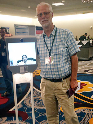 Richard Lander standing with a Beam Robot with Kavita on the front screen.