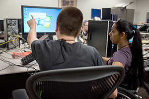 Two students work on a computer in a computer lab.