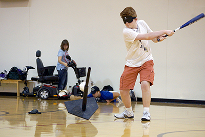 -	Phase I Scholar Jarrod takes a swing at beeping baseball at the accessible sports expo during Summer Study 2016.