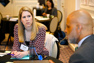 A participant listens to another at her table.