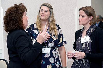 Three participants discuss ideas.