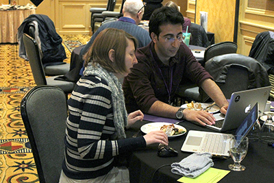 One participant uses a computer while another discusses ideas.