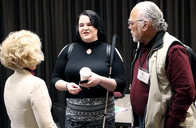 Two participants talk to AccessCyberlearning director Sheryl Burgstahler.