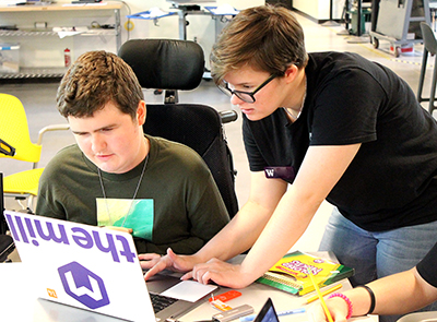 A mentor works with a student in a wheelchair on a computer.