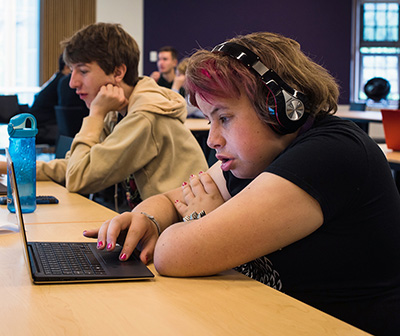 A student wears headphones and works on the computer.