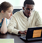 A mentor works with a student on a computer project