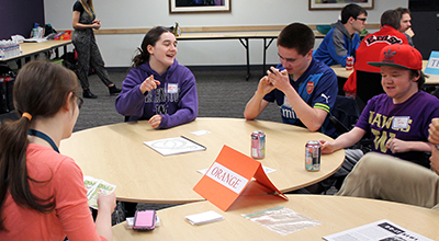 A group of students get to know each other while playing cards at a campus meet up.