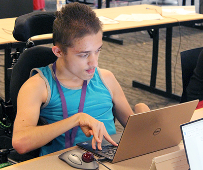 A student uses a laptop to write code for a computer science project.