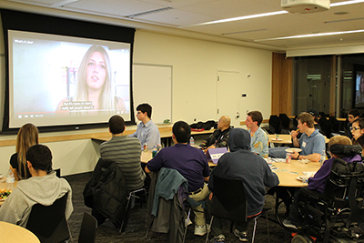 DO-IT Ambassadors watch a DO-It produced video at the February 2016 pizza and networking event.